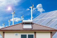 Solar panel for hot water system on roof and wind turbines blue. Sky background , Energy saving and natural energy concept Royalty Free Stock Image