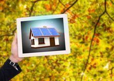 Solar panel house on tablet with businesswoman hand in the park. Digital composite of solar panel house on tablet with businesswoman hand in the park Stock Photos