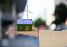 Solar panel house and windmill on hand  in the city Stock Images