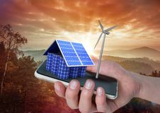 Solar panel house and windmill on hand with mountains behind Stock Image
