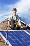 Solar panel installation. Man installing alternative energy photovoltaic solar panels on roof Royalty Free Stock Image
