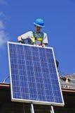Solar panel installation. Man installing alternative energy photovoltaic solar panels on roof Stock Photography