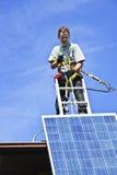 Solar panel installation. Man installing alternative energy photovoltaic solar panels on roof Royalty Free Stock Photography