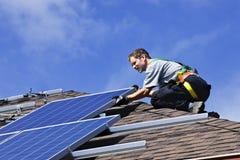 Solar panel installation. Man installing alternative energy photovoltaic solar panels on roof Royalty Free Stock Photos