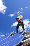 Solar panel installation. Worker installing alternative energy photovoltaic solar panels on roof Stock Images