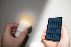Solar panel and light bulb in hand. Solar energy photovoltaic panel and light bulb in hand Royalty Free Stock Photos