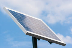 Solar panel mounted on a pole towards right with clouds reflecti Royalty Free Stock Image