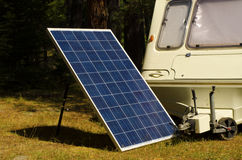 Solar panel with old caravan in a pine forest Stock Image