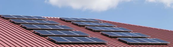 Solar panel pattern on red roof tile. Stock Photo