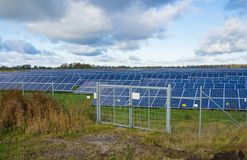 Solar panel or photovoltaic farm behind metal chainlink fence on green field with dramatic cloudy sky in North Germany Stock Images