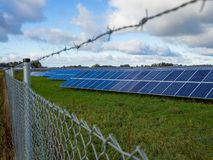 Solar panel or photovoltaic farm behind metal chainlink fence on green field with dramatic cloudy sky in North Germany Stock Photos
