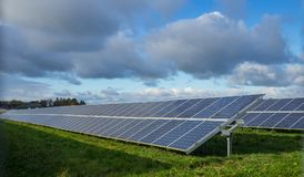 Solar panel or photovoltaic farm on green field with dramatic cloudy sky in North Germany Stock Photos