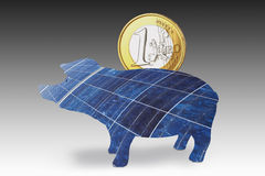 Solar panel piggy bank with one euro coin against gray background. Stock Photo