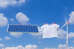 Solar panel and plain white T- shirt and wind turbine hanging on clothes line Royalty Free Stock Image
