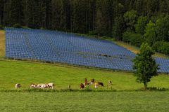 Solar panel power system by the forest. Solar panel power system constructed in a farmland by the forest in Austria royalty free stock photos