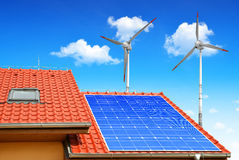 Solar panel on the roof of the house. In the background wind turbines Stock Photos