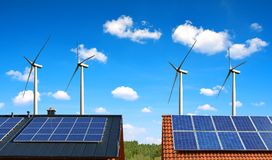 Solar panel on the roof of the house in the background wind turbines and blue sky. Royalty Free Stock Image