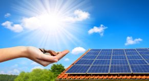 Solar panel on the roof of the house and coins in hand. Royalty Free Stock Photography