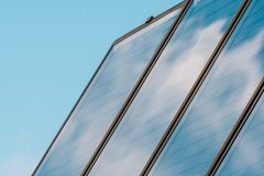 Solar panel on the roof of the house. Solar energy. The panel reflects blue sky with clouds Royalty Free Stock Images
