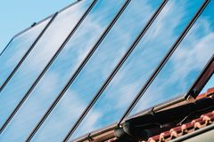 Solar panel on the roof of the house. Solar energy. The panel reflects blue sky with clouds Stock Photography