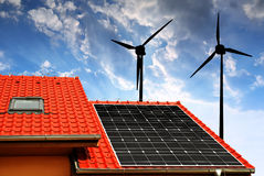 Solar panel on the roof of the house and wind turbines Stock Photos