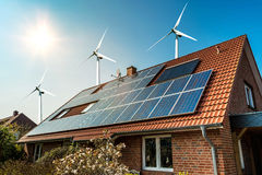 Solar panel on a roof of a house and wind turbins arround royalty free stock photography