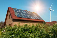 Solar panel on a roof of a house and wind turbins arround. Concept of sustainable resources Stock Photos