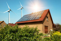 Solar panel on a roof of a house and wind turbins arround. Concept of sustainable resources Royalty Free Stock Images