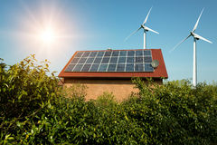 Solar panel on a roof of a house and wind turbins arround. Concept of sustainable resources Stock Images
