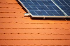 Solar panel on the roof. Solar panel on the red roof of a private house producing electricity, industrial backround with empty space for text Royalty Free Stock Photos