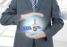 Solar panel satellite between businessman  hands with light. Digital composite of solar panel satellite between businessman  hands with light Stock Photo