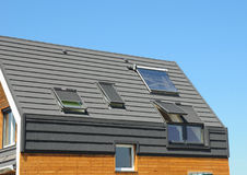 Solar panel and solar water heater  on the modern house roof with skylights and dormer outdoor for energy efficiency. Royalty Free Stock Image