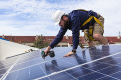 Solar panel technician. With drill installing solar panels on roof Royalty Free Stock Images