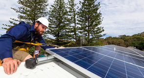 Solar panel technician. With drill installing solar panels on roof Stock Photography