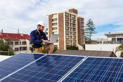 Solar panel technician. With laptop on house roof Stock Image