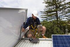 Solar panel technician. Measuring solar output on roof Stock Photos