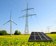Solar panel with wind turbine and electricity pylons. Stock Photo