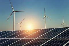 solar panel and wind turbine with sunrise background stock image