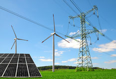 Solar panel with wind turbines and electricity pylon on meadow. Concept of sustainable resources stock image