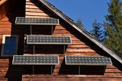 Solar panel on a wooden house Stock Photos