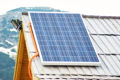 Solar panel on the wooden roof at mountrain area house. Renewable clean green energy saving efficient solar panels on small Royalty Free Stock Photos