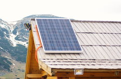 Solar panel on the wooden roof at mountrain area house. Renewable clean green energy saving efficient solar panels on small Stock Photography