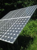 Solar panel by the woods. A solar panel sits by the edge of the woods collecting the suns rays Royalty Free Stock Images