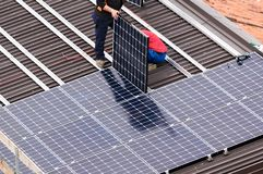 Solar panel and workers. royalty free stock image