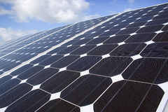 Solar Panels. A row of solar panels installed on a rooftop and angled towards the sun to generate solar power. Photovoltaic cells are used for generating clean stock image