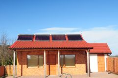 Solar panels. Front of bungalow with solar panels on red roof. Blue sky in background Royalty Free Stock Image