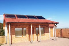 Solar panels. Small bungalow with solar panels on red roof under blue sky Royalty Free Stock Image