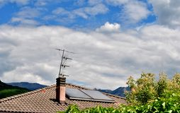 Solar panels. Brick house with a roof and solar panels to produce electricity from the sun royalty free stock photography