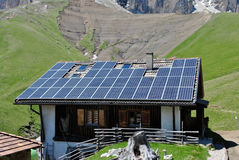Solar panels. House roof with solar panels  background of the Dolomites mountains Stock Photos