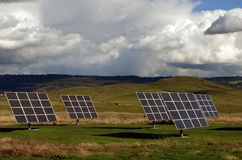 Solar Panels. In a pasture with cows and cloudy sky Stock Photo